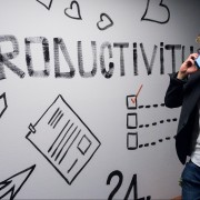 """Businessman on phone in front of whiteboard that says """"productivity."""""""