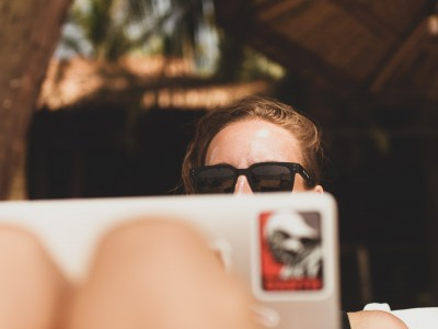 Woman wearing sunglasses working on laptop