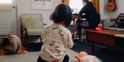 Mother works from home as child plays in foreground