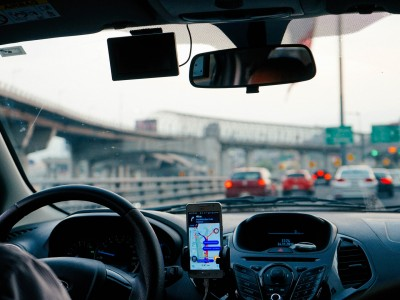 View out windshield as person drives and looks at directions on phone.