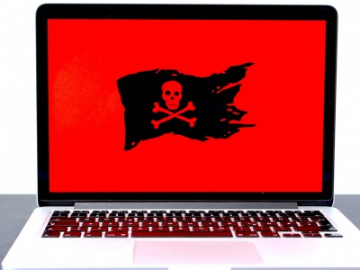 Laptop displaying a pirate flag / jolly roger on a red screen