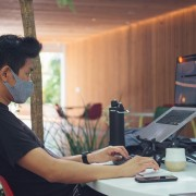 Office worker with mask reading laptop