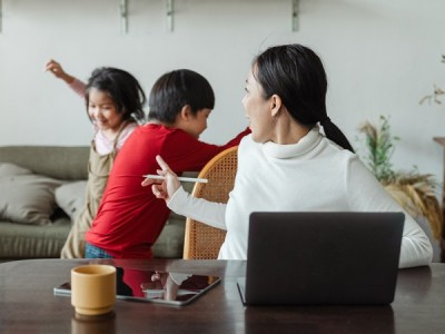 Mother trying to work from home while her two kids plays by her side