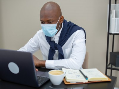 Man wearing face mask working at his desk on laptop
