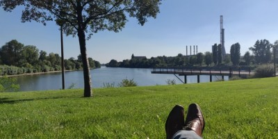 Person with legs crossed laying on grass near a river- Remote Report