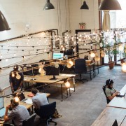 People working on laptops at tables in the Bat Haus Coworking and Event Space in Brooklyn- Remote Report