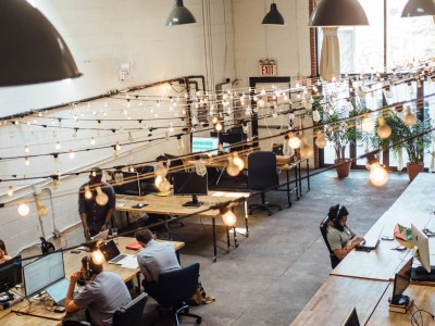 People working on laptops at tables in the Bat Haus Coworking and Event Space in Brooklyn.