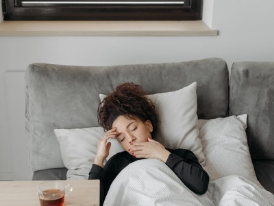 A woman laying sick in bed