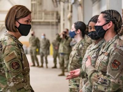 Air Force members wearing masks talk at Altus Air Force Base, Okla.