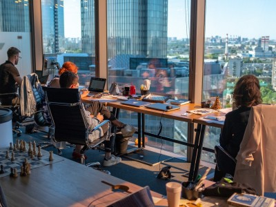 Workers on computers near window with city view