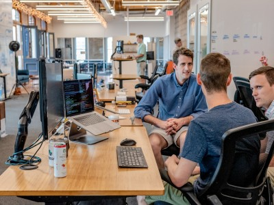 Three sitting workers talk at office