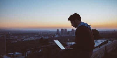 Man on building ledge with laptop