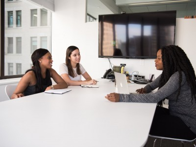 Three women sitting at conference table discuss business