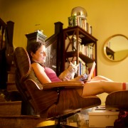 Woman lounging in recliner with laptop and cat