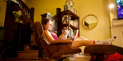 Woman lounging in recliner with laptop and cat– Remote Report