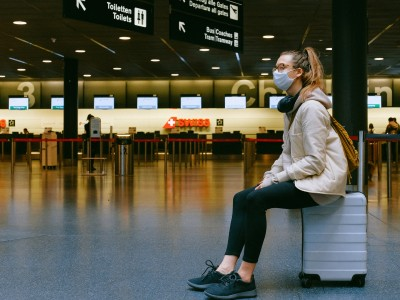 Person sitting on suitcase at airport