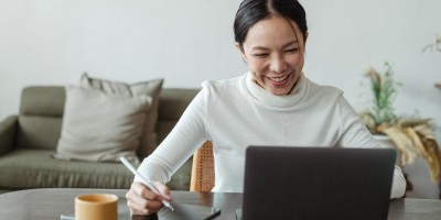 Woman smiling as she works on her laptop at the table