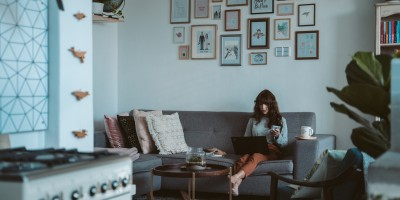 Woman on couch staring at laptop in her apartment