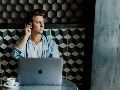 Man on laptop at cafe with headphones