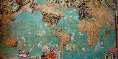 World map with money pinned to it