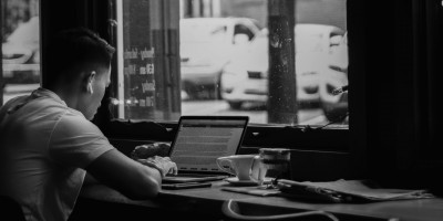 Person working on laptop at cafe- Remote Report