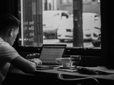 Person working on laptop at cafe