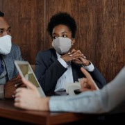 Three sitting at desk with masks on