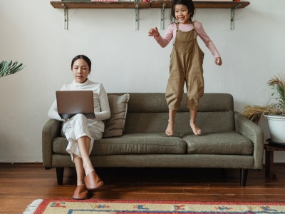 Woman on laptop while child jumps