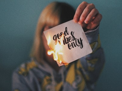 """Woman holding burning napkin that reads """"good vibes only"""""""