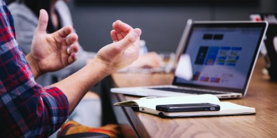 Remote worker gesturing with hands on video call– Remote Report