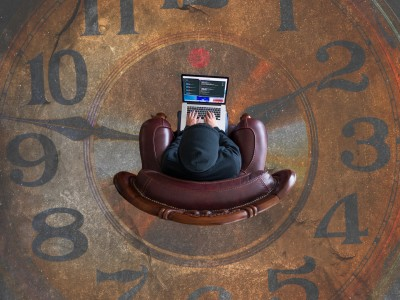 Remote worker sitting in chair on floor picture of clock
