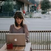 Woman working on laptop sitting next to street