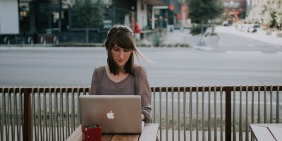 Woman working on laptop sitting next to street– Remote Report