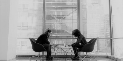 Two women facing each other while working on laptops