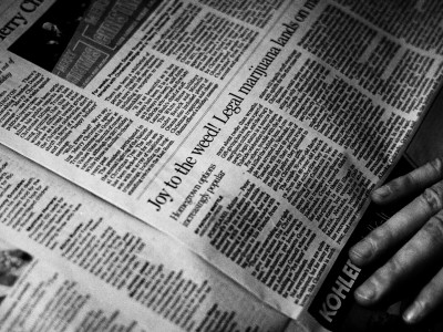 Picture of newspaper with hand on page