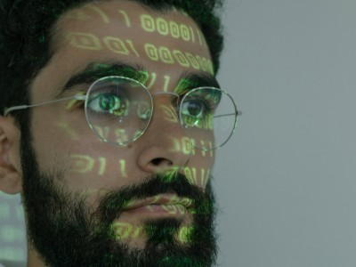 Programmer with glare from computer screen on his face