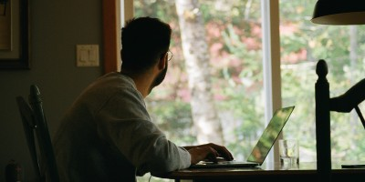 Man working on laptop staring out window