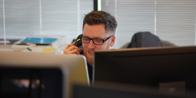 Employee on phone and computer– Remote Report