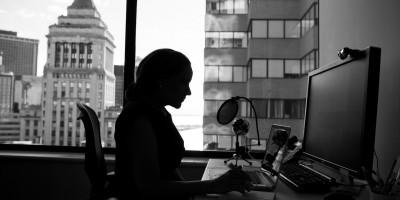 silhouette of person on computer with buildings background