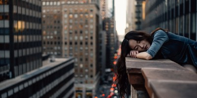 Woman resting head on balcony in New York City