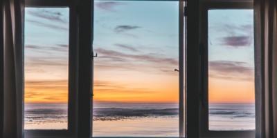Sun setting behind three large windows