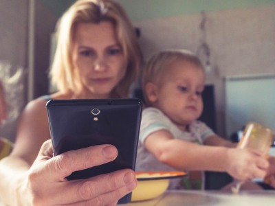 A woman uses smartphone while sitting with children, working mom