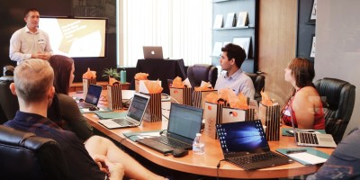 Manager leads meeting around conference table– Remote Report