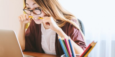 Woman biting pencil as she looks at her laptop– Remote Report