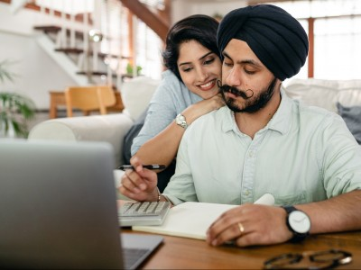 Remote worker hugged by partner while on laptop